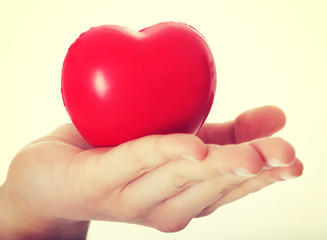 Red heart held on a female's hand.