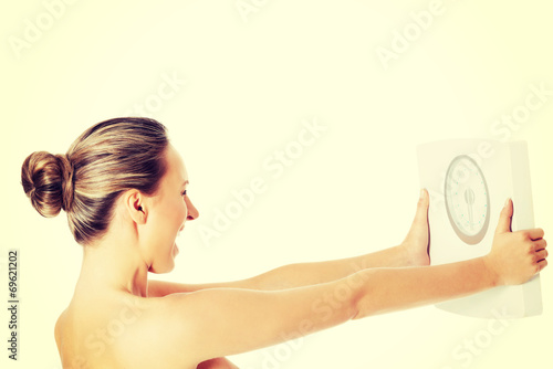 canvas print picture Nude topless woman holding scale.
