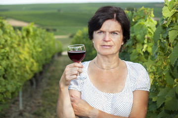 Woman in vineyard holding wine glass