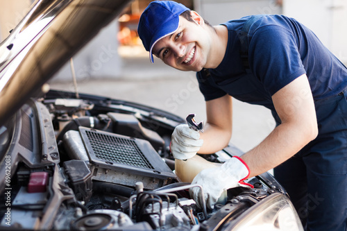 Mechanic fixing a car engine - 69622088