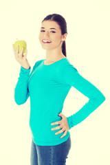 Beautiful casual woman holding an apple.