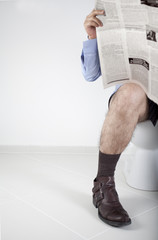 Man reading newspaper in the bathroom