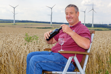 Man sitting with wine bottle in cornfield
