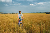 Boy  on a bicycle on mellow rye field poster