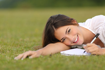 Happy woman lying on the grass and writing in a notebook