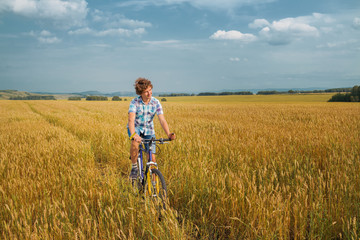 Boy  on a bicycle on mellow rye field