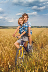Portrait of a teen on a bicycle traveling in rye field