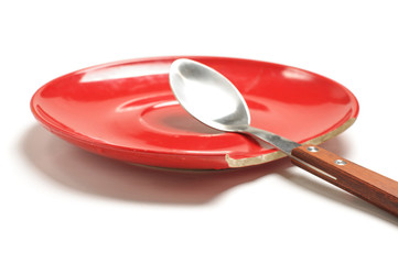 Spoon in the red broken plate isolated