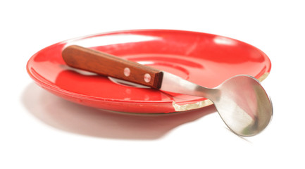 Broken plate with the spoon isolated on the white background