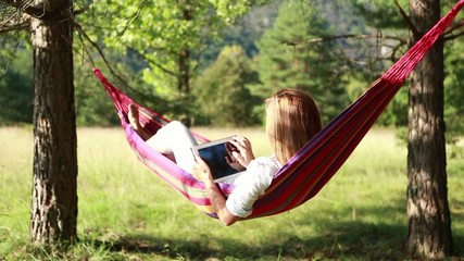 Young woman relaxing in a hammock with digital tablet
