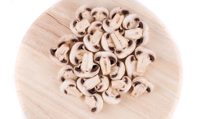 White mushrooms on wooden board.