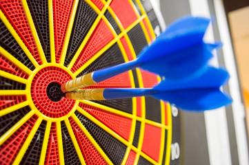 two darts in bullseye of dartboard