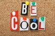 The phrase Be Cool in cut out letters on a cork notice board