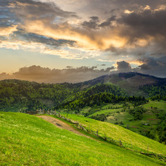 fence on hillside meadow in mountain at sunrise