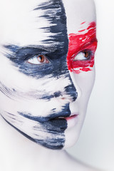 Woman with white makeup and red and black stripes paint