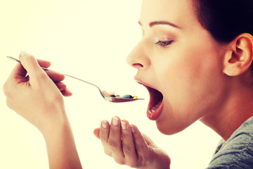 Young casual woman eating pills on a spoon.