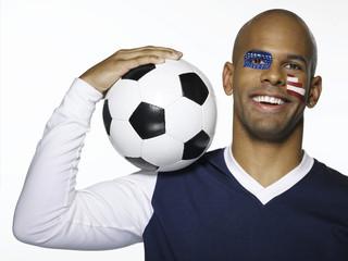 Mann mit USA-Flagge auf Gesicht gemalt , hält Fußball