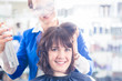 Постер, плакат: Hairdresser styling woman hair in shop