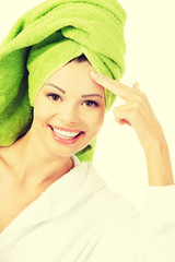 Beautiful woman in bathrobe and turban is touching her forehead.