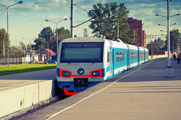 Modern suburban electric train standing at the station, photo wi
