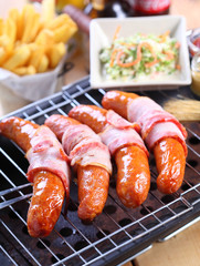Grilled sausages with bacon and salad vegetables