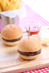 Two homemade hamburgers on wooden board