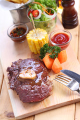beef steak with spices on wood plate over wooden table