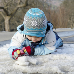 Child plying with snow and ice