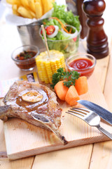 pork steak with spices on wood plate over wooden table