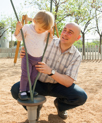 father and  daughter playing on playground.
