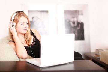 junges Mädchen am Laptop mit Kopfhörern
