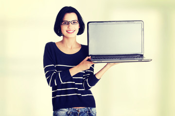 Woman holding and showing screen of 17 inch laptop
