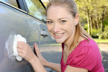 Frau poliert Auto-Lack mit Watte
