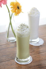 ice green tea and milk smoothie on a wood table