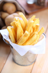 French fries in metal cup on wood table