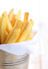 closeup of French fries in metal cup on wood table