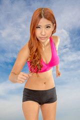 Beautiful Asian woman jogging with clouds behind her