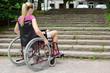 Frau im Rollstuhl vor Treppe als Hindernis - 69630679