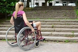 Frau im Rollstuhl vor Treppe als Hindernis