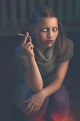 Teen girl sits and smokes