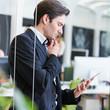 canvas print picture - Mann im Büro schaut auf Tablet Computer