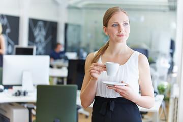Frau im Büro trinkt Kaffee in der Pause