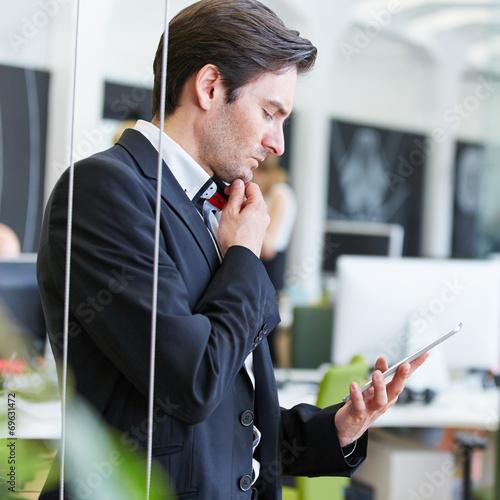 canvas print picture Mann im Büro schaut auf Tablet Computer
