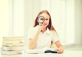girl reading book with magnifier at school