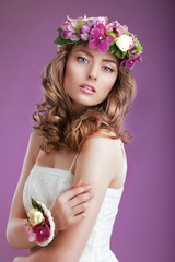 Exquisite Woman with Wreath of Flowers. Lady with Frizzy Hair