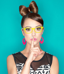 Young attractive fashionable woman with finger on lips