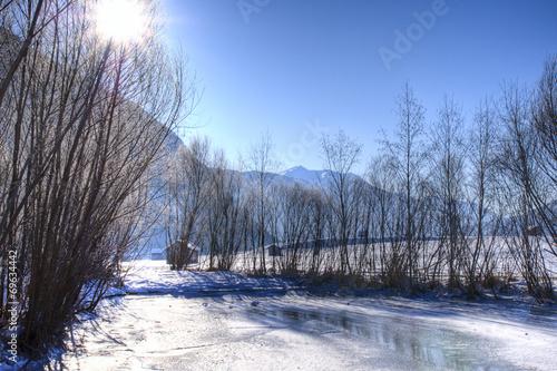 canvas print picture Gegenlicht in verschneiter Flusslandschft