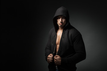 strong man wearing hoodie isolated on black background with copy