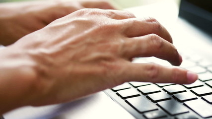 Hand Write on  a Laptop Keyboard Close-Up