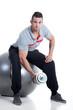 Junger sympatischer Sportler mit Hantel beim Training